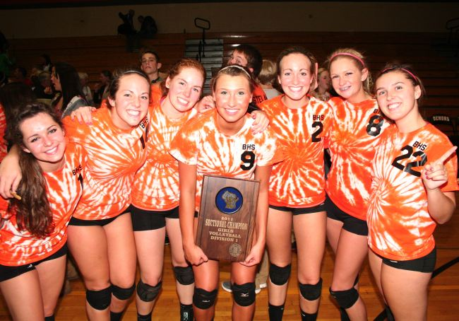 Senior members of the Burlington High School girls' volleyball team, Cat Zimmermann (from left), Cassidy Robers, Bridget Vos, Katie Drohner, Emma Ketterhagen, Mackenzie Schneider and Casey Roberts celebrate with their trophy after winning the sectional Saturday.  (Photo by Jennifer Eisenbart)
