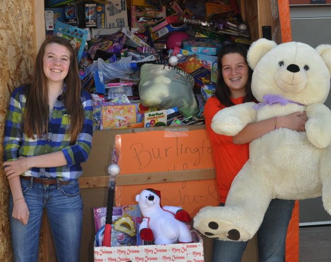 Burlington High School sophomores Bianca Clayton (left) and Madison Epping gather with some of the 2,707 toys students, staff and community members donated to the Toys for Tots campaign. The school's donation won a concert from American Idol winner Scotty McCreery. (Photo by Ed Nadolski)