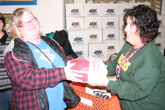 Barbara Binet (left) accepts a turkey from volunteer Patty McManus at Love Inc. Monday. Binet's family is among the nearly 700 that are getting their Thanksgiving meal courtesy of the agency this year. (Photo by Jennifer Eisenbart)