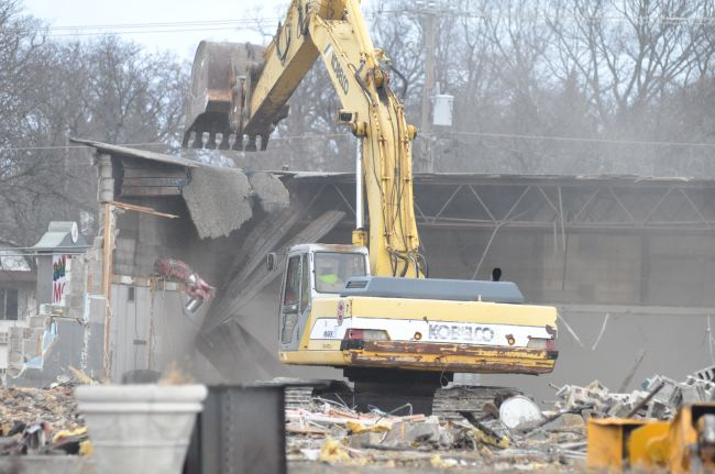One of the final walls of the former City of Burlington Department of Public Works facility tumbles to the ground Tuesday as a demolition crew takes down the building at 824 Milwaukee Avenue. The city has an accepted offer to sell the site to a developer of an O'Reilly Auto Parts store. (Photo by Ed Nadolski)